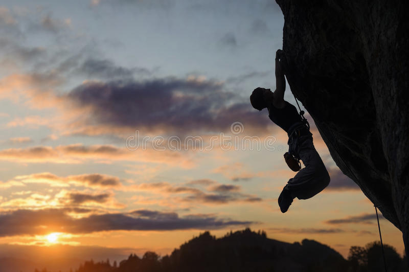 攀登陡峭的岩石墙壁的运动妇女剪影 图库摄影