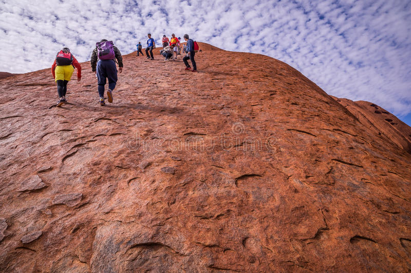 攀登Uluru艾瑞斯岩石的游人 免版税库存照片