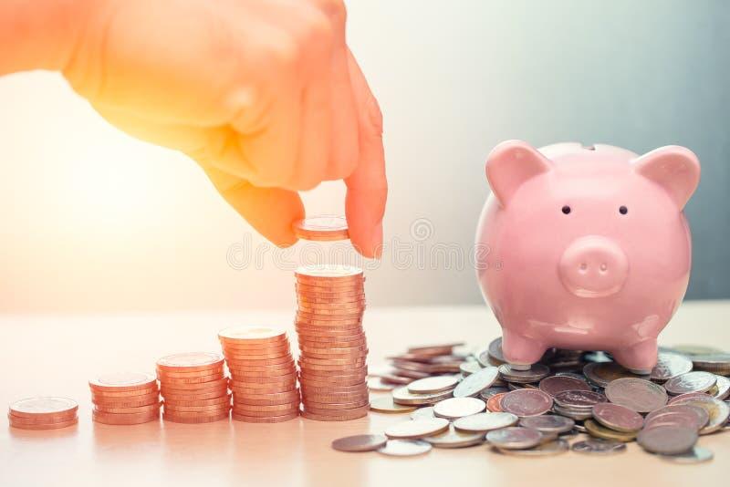 攒钱向猪银行,有堆的存钱罐硬币 免版税库存图片