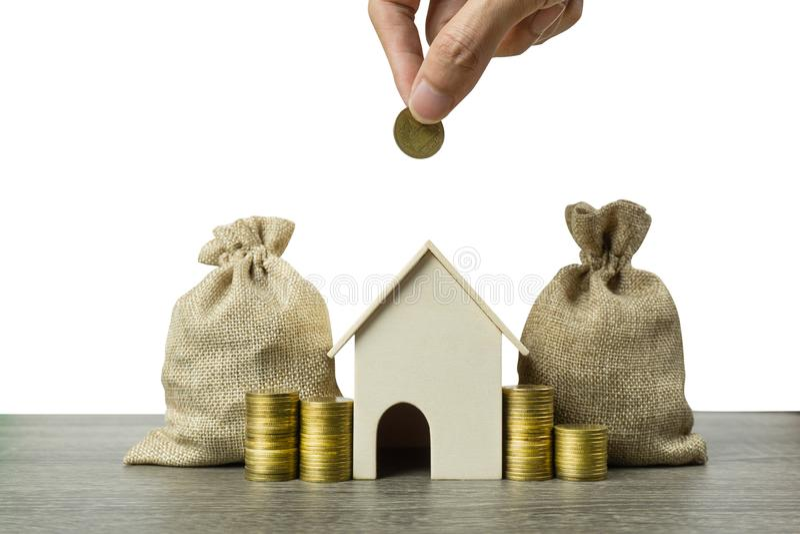 攒钱或物产投资或买一个新的家庭概念 与堆的一个小屋模型硬币和金钱袋子在木桌上 图库摄影