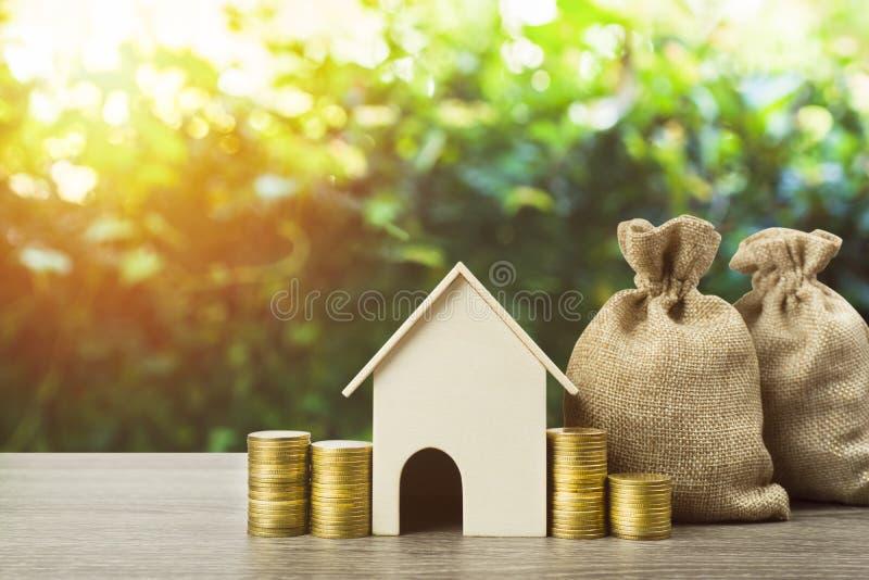 攒钱或物产投资或买一个新的家庭概念 与堆的一个小屋模型硬币和金钱袋子在木桌上 免版税库存图片