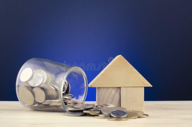 攒钱概念,在玻璃瓶子的硬币在木的书桌上说出 库存图片