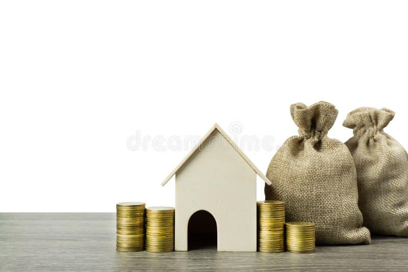 攒钱,房屋贷款,抵押,未来概念的物产投资 与堆的一个住所房子模型硬币和金钱 图库摄影