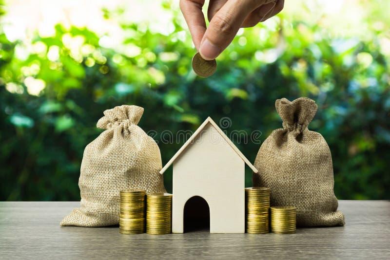 攒钱,房屋贷款,抵押,未来概念的物产投资 投入在小住所的人手金钱硬币 库存图片