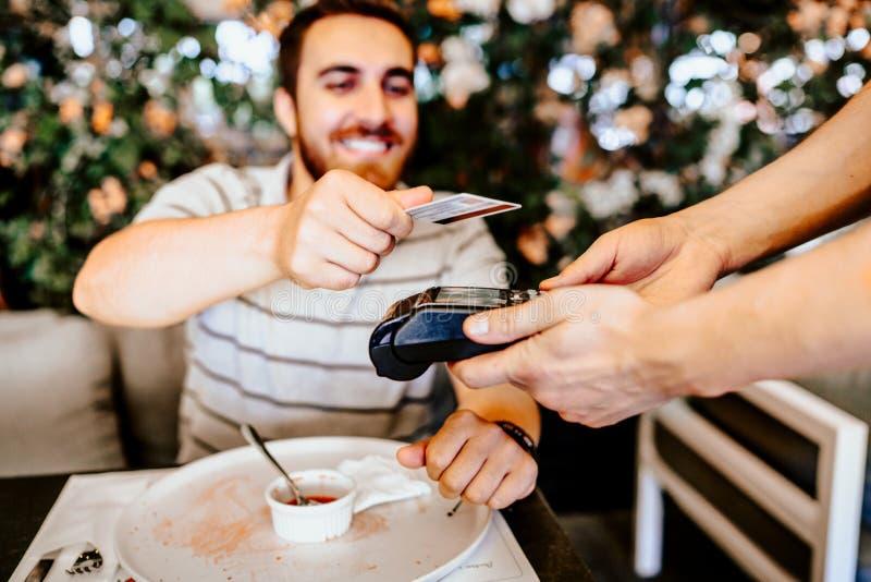 支付与不接触的信用卡的午餐的餐馆的微笑的顾客 不接触的技术细节 免版税库存图片
