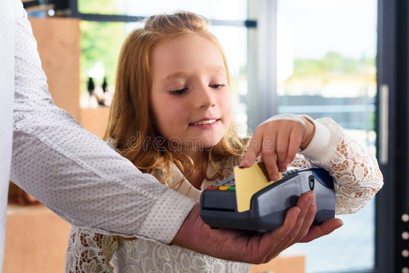支付与信用卡的小女孩 免版税库存照片