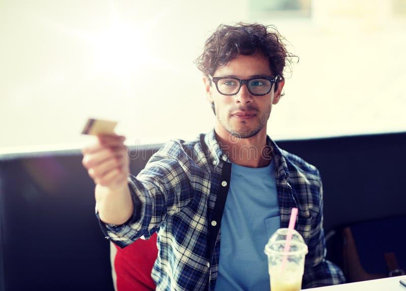 支付与信用卡的愉快的人在咖啡馆 免版税库存照片
