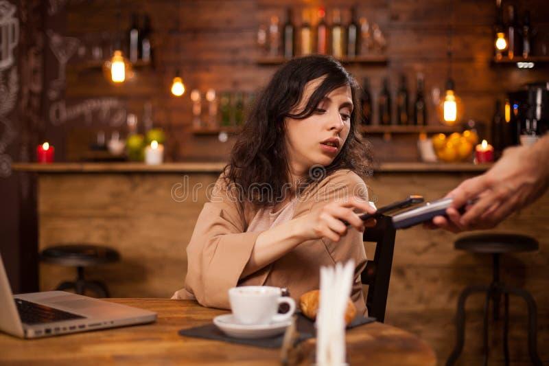 支付与信用卡的美丽的年轻女人照片在咖啡馆 免版税库存图片