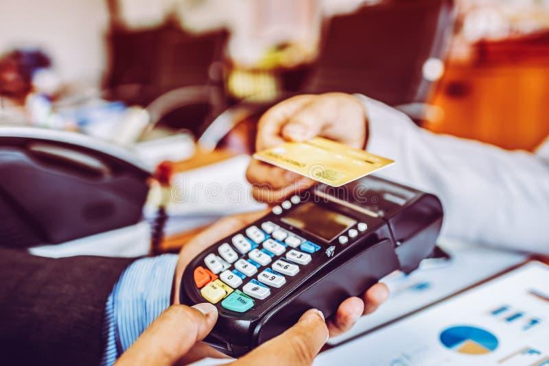 支付与NFC技术不接触的信用卡的商人顾客的手 库存图片