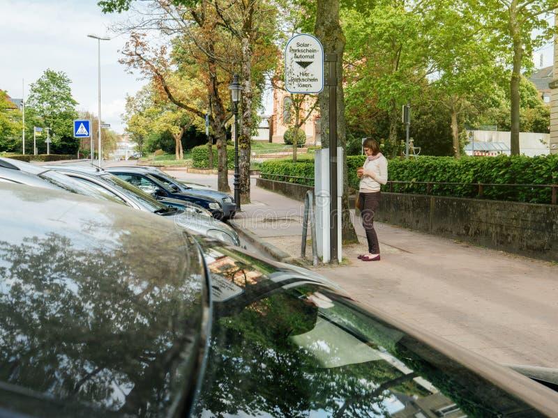 支付停放的妇女在德国违规停车罚单付款ma 库存照片