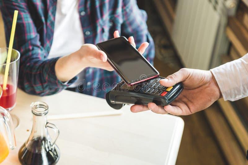 支付在与不接触的智能手机付款的咖啡馆的年轻可爱的妇女 库存照片