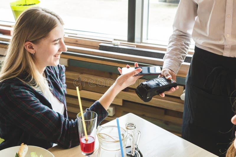 支付在与不接触的智能手机付款的咖啡馆的年轻可爱的妇女 免版税图库摄影