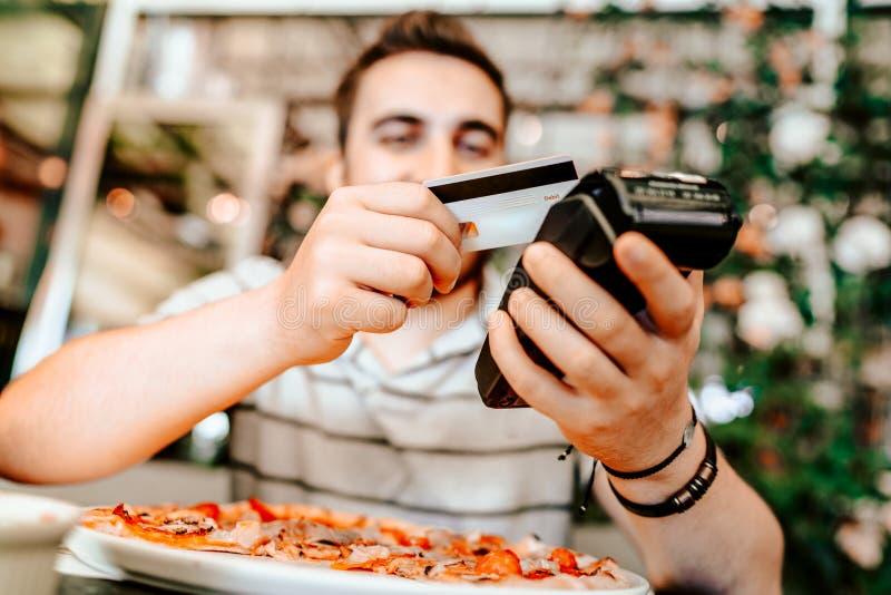 支付在餐馆的微笑的人使用智能手机 与不接触的信用卡的流动支付的技术 库存照片