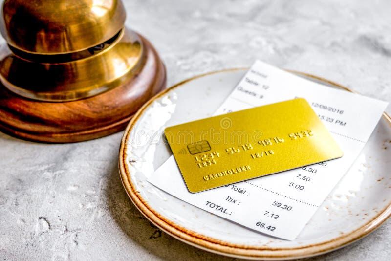 支付支票在咖啡馆的午餐与在石桌b上的信用卡 库存图片