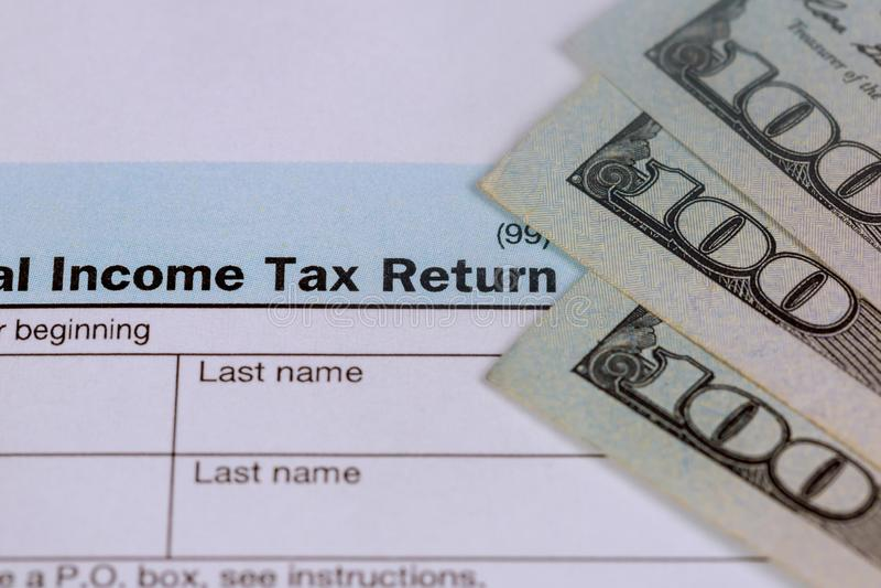 支付税概念美国与100张美元票据的报税表1040 库存照片