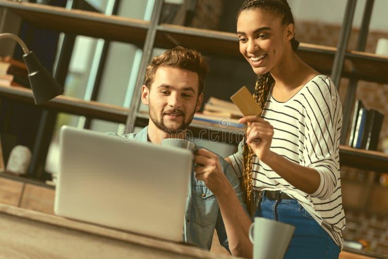 支付网上购买的快乐的青年人 库存图片