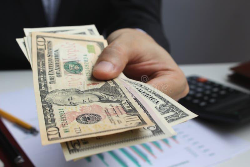 支付美元,手用途在办公桌上的美元金钱  免版税库存照片