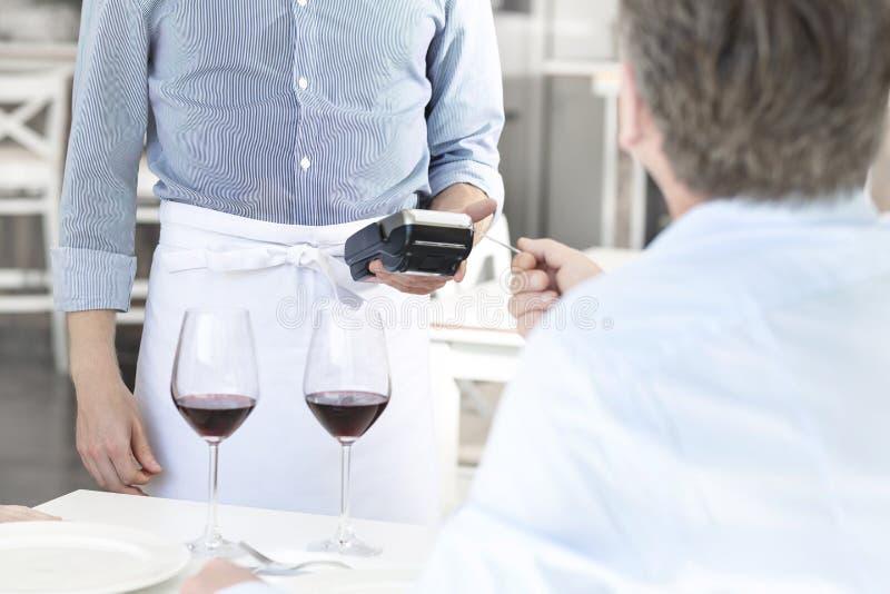 支付通过信用卡的成熟顾客在餐馆 库存图片