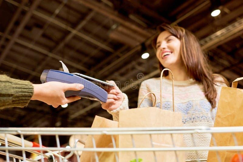 支付通过智能手机的妇女在超级市场 免版税库存图片