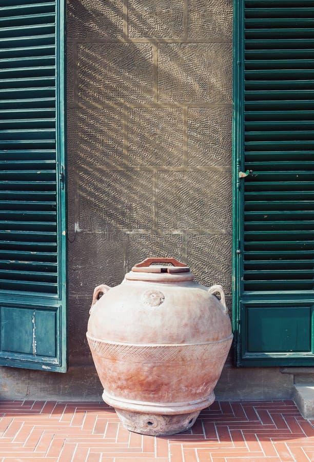 支持一个老房子的墙壁的古色古香的黏土瓶子在意大利 免版税库存图片
