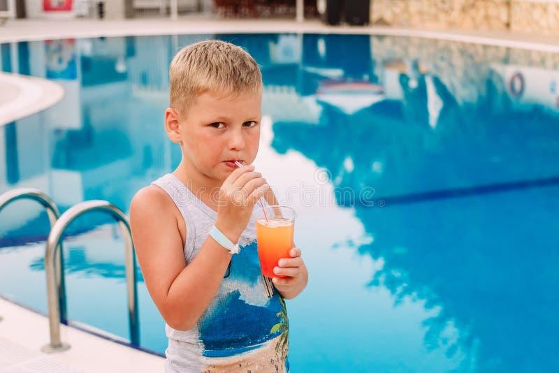 支持一个蓝色室外水池喝橙色水果鸡尾酒的一个逗人喜爱的白肤金发的白种人七岁的男孩通过秸杆 免版税库存图片