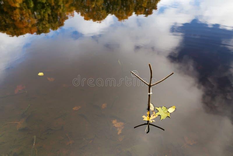 支持一根钓鱼竿在秋天在森林湖 库存照片