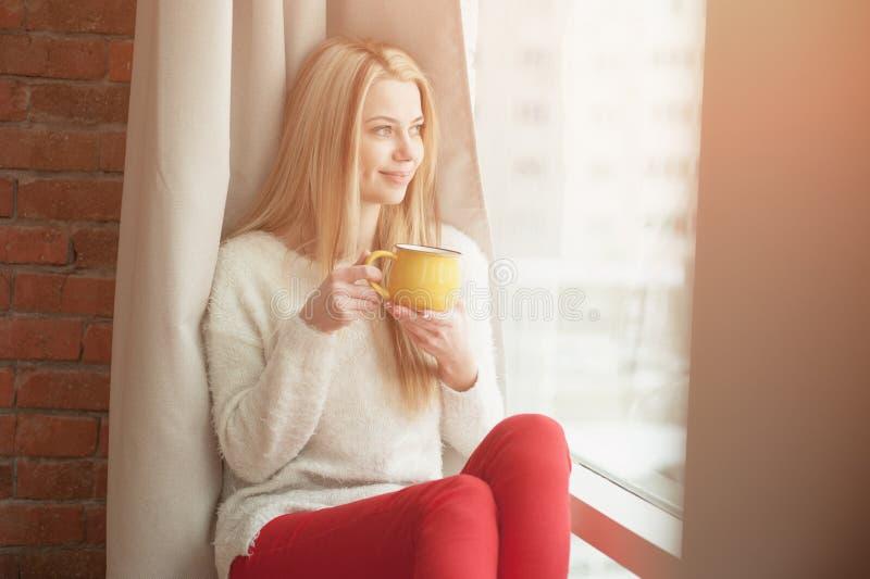 支持与一杯咖啡的少妇窗口,看外部和微笑 自然室外光 免版税库存照片