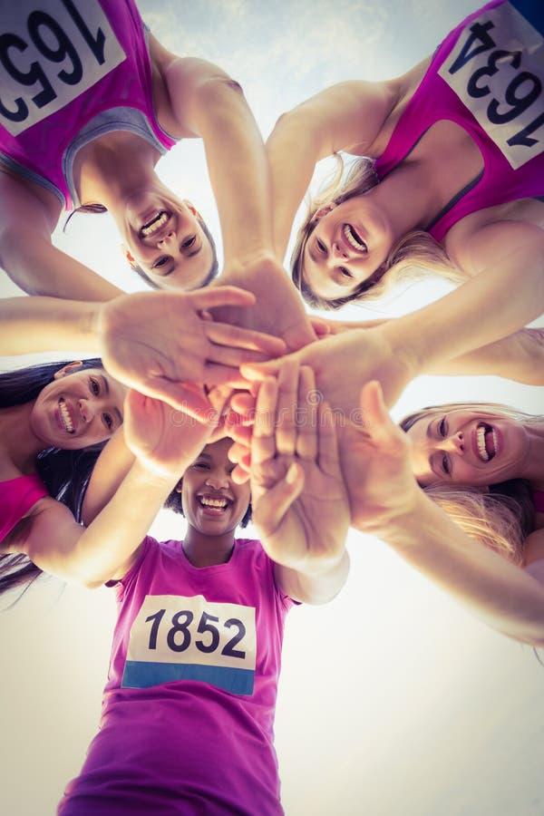 支持乳腺癌马拉松的五个微笑的赛跑者 免版税库存图片