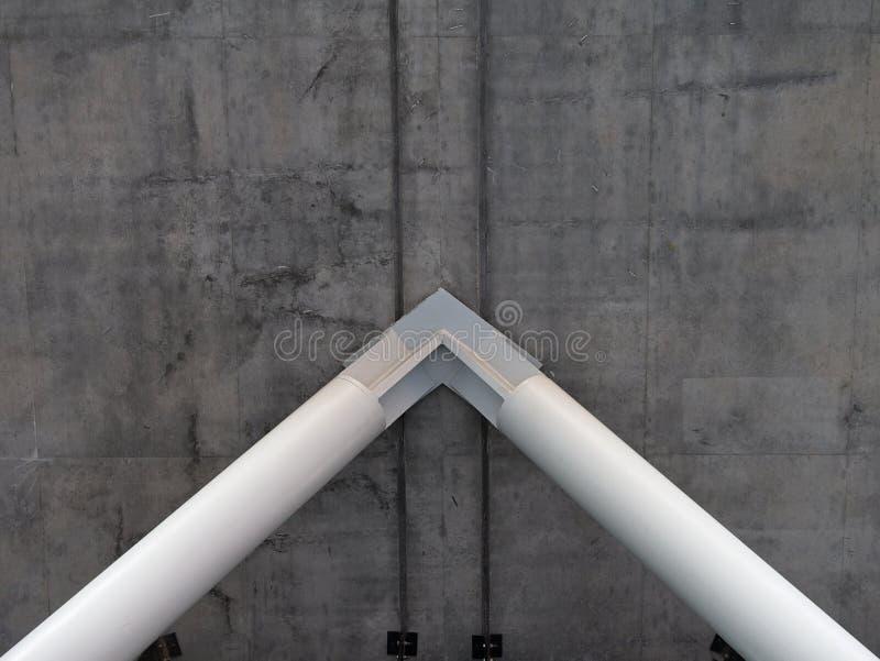 支持厚实的灰色混凝土的白色钢柱子 免版税库存图片