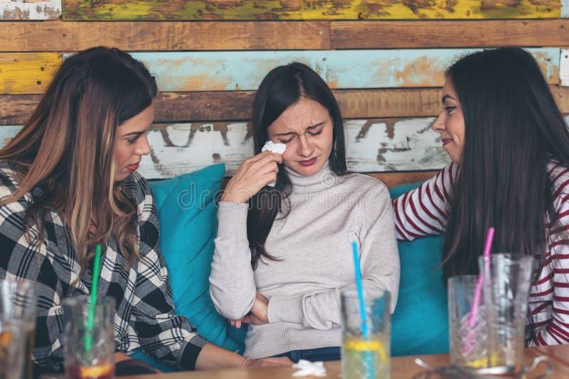 支持和慰问哭泣的年轻女人的女朋友在餐馆 图库摄影
