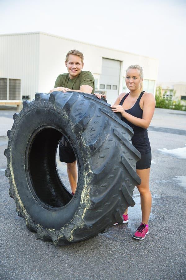 支持在健身俱乐部之外的确信的运动员巨大的轮胎 免版税库存图片