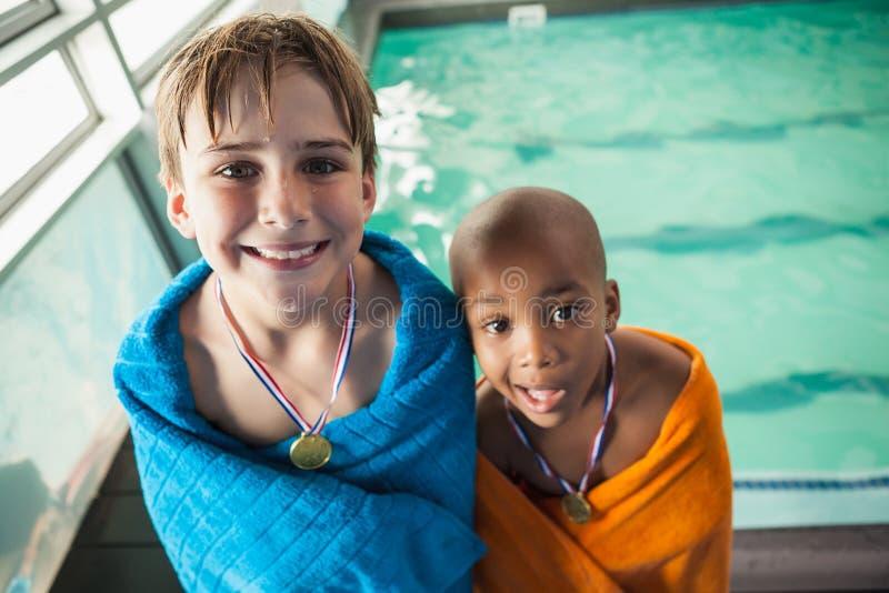 支持在毛巾的小男孩水池与奖牌 库存照片