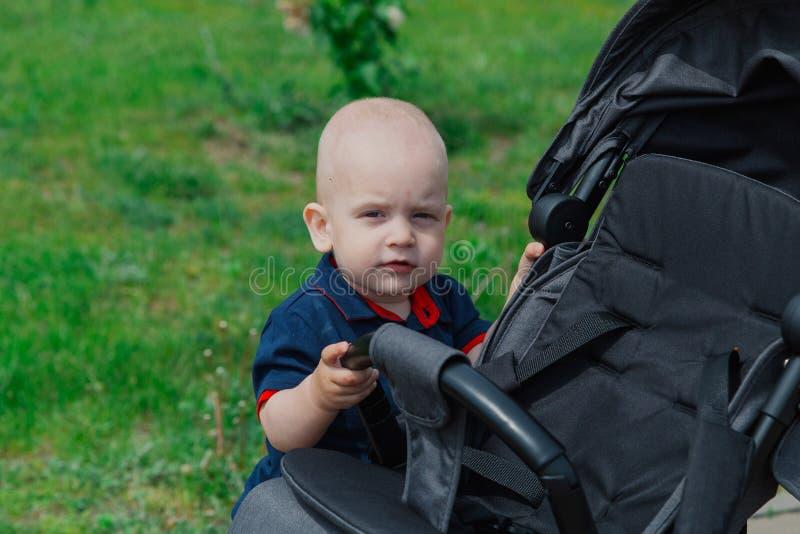 支持在温暖的夏时的一个小孩子一辆婴儿车 库存照片