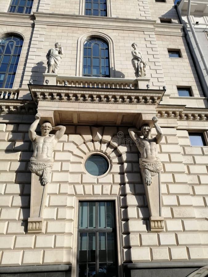 支持宫殿的阳台的有妇女雕塑的人雕塑  免版税图库摄影