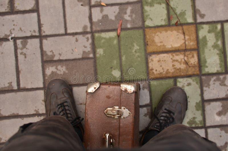 支持带着手提箱的男性旅客侧视图画象街道 免版税库存图片