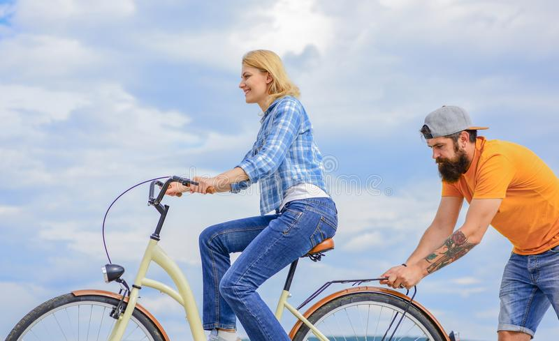 支持帮助相信你自己 支持和友谊 妇女乘坐自行车天空背景 人帮助保持平衡 免版税库存照片