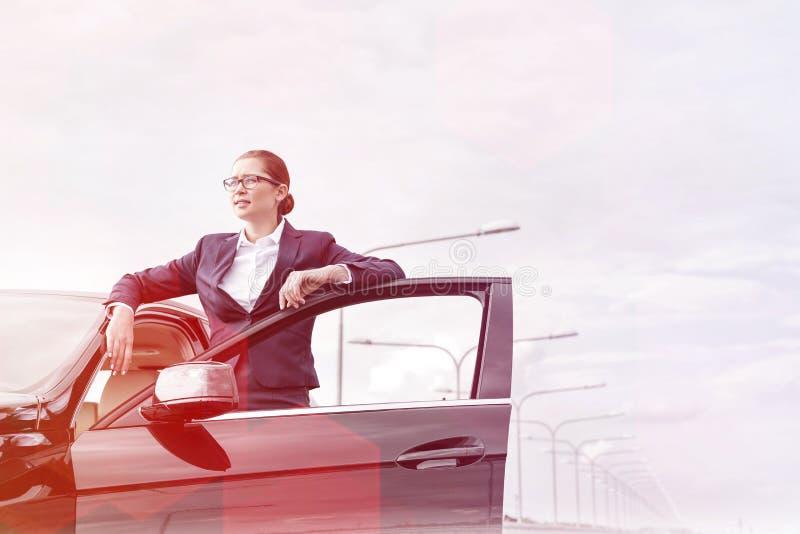 支持开放车门的确信的女实业家反对天空 库存照片