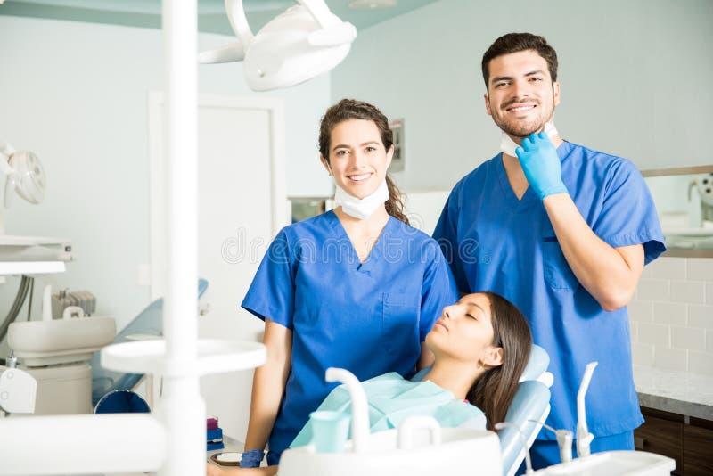 支持患者的微笑的牙医画象在诊所 库存照片