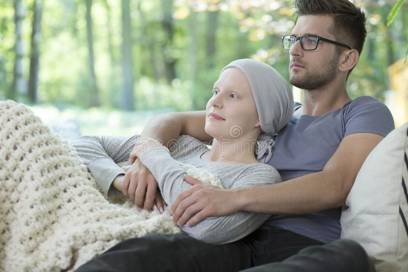 支持有乳腺癌的男朋友病的女孩,当放松时 免版税库存图片