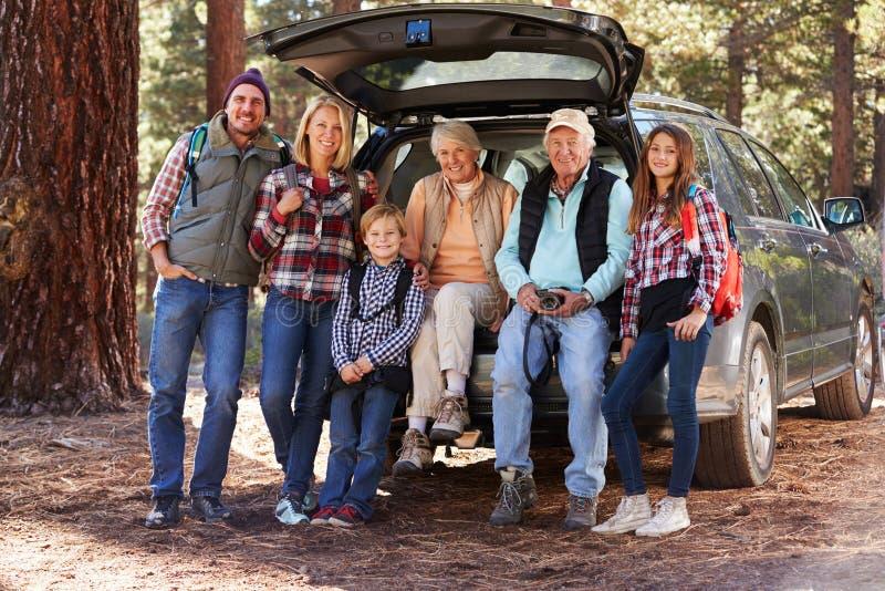 支持汽车的多一代家庭在森林远足前 库存图片