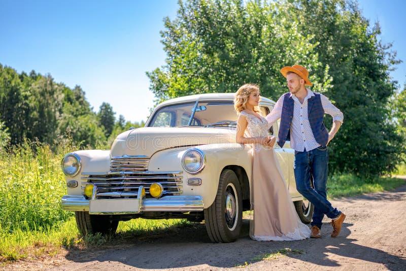 支持汽车的美好的年轻夫妇 库存图片