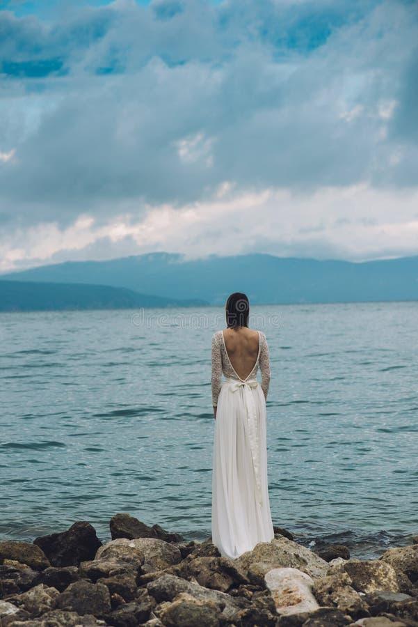 支持海的美丽的新娘 目的地婚礼概念 婚姻在异乎寻常的海岛上 免版税库存照片