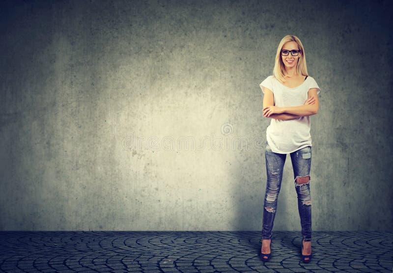 支持混凝土墙的年轻确信的愉快的妇女 免版税库存图片