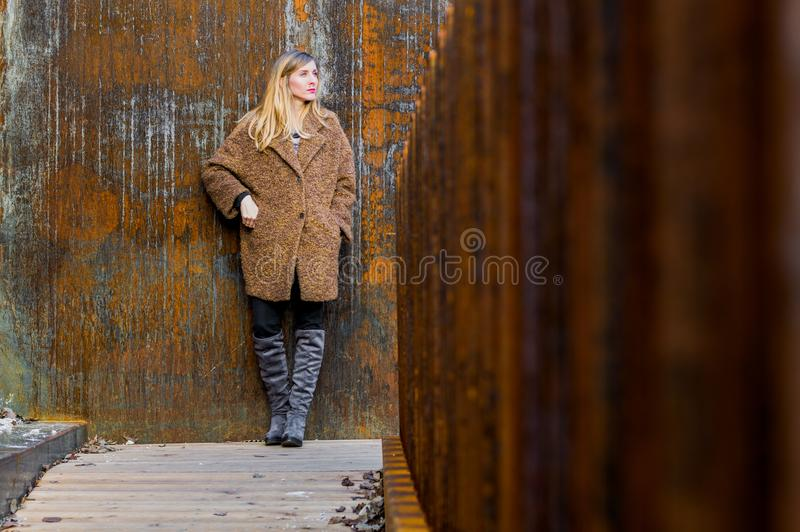 支持生锈的墙壁的金发碧眼的女人 库存照片