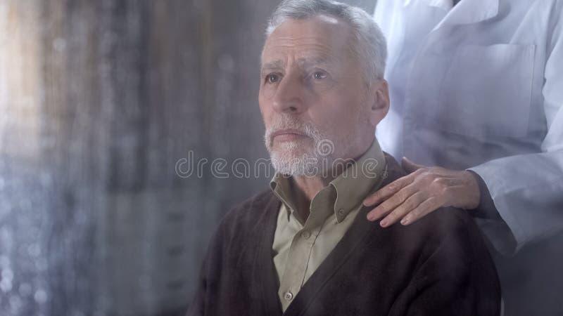 支持病的老人的医生,拿着耐心肩膀,艰难,寂寞 免版税库存图片