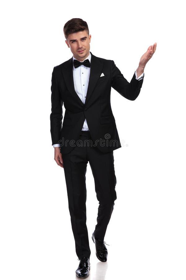 支持的黑无尾礼服礼物的年轻帅哥 免版税库存图片
