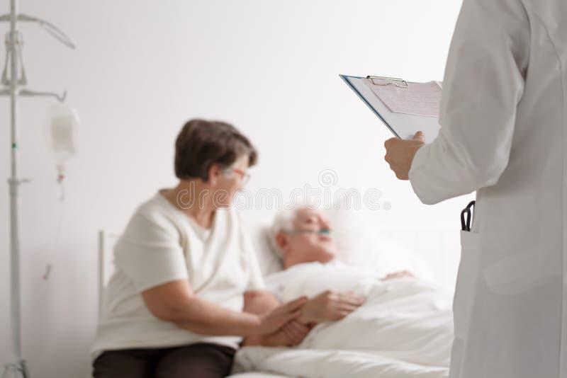 支持的妻子听的医生` s诊断 免版税库存图片