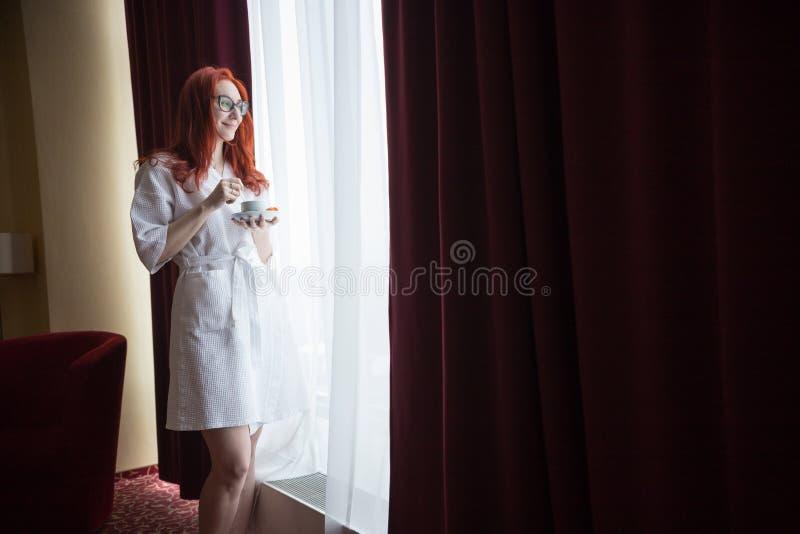支持窗口在酒店房间和拿着一杯咖啡的红头发人妇女 免版税图库摄影