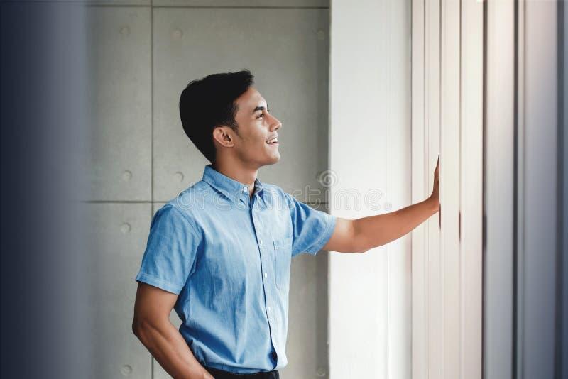 支持窗口的愉快的商人画象在办公室 看外部和微笑 免版税图库摄影