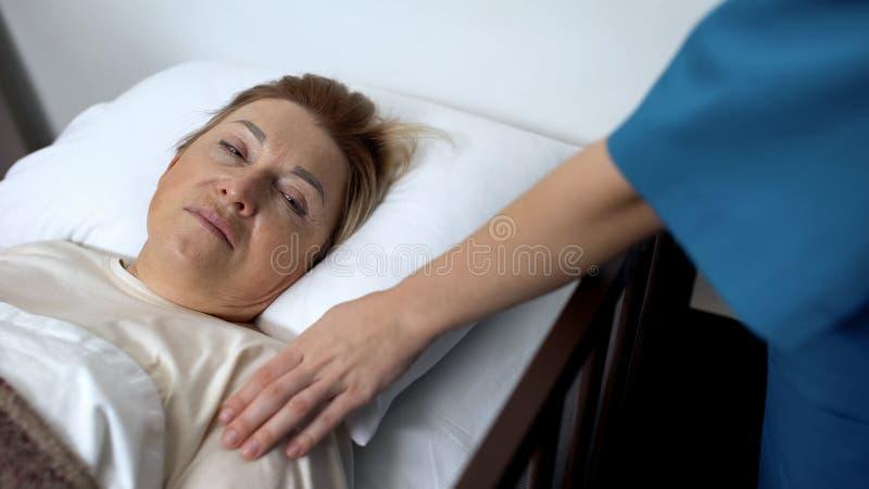 支持绝望年长患者的关心的护士在医院病床,疾病上 免版税库存照片
